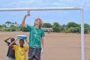 Local children assist a volunteer painting a frame on a building project in Ghana
