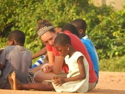 A young girl and a Projects Abroad volunteer read together in Ghana