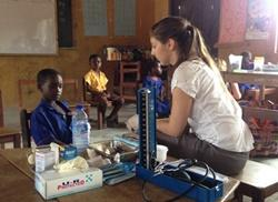 Projects Abroad volunteer assists a young boy on a medical outreach in Ghana