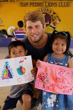 Two children sharing their artwork with a male volunteer in Belize