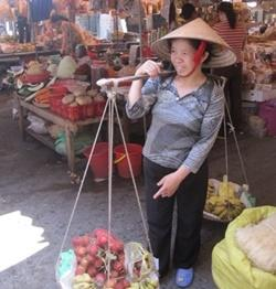 A Vietnamese lady sells fruit at a market