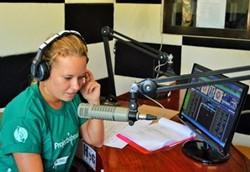 A Projects Abroad volunteer speaks into a microphone at her Journalism placement in Asia