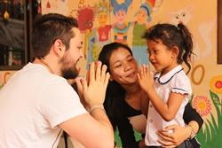 Projects Abroad Medicine volunteers plays with local Cambodian children during a medical outreach programme in Phnom Pehn